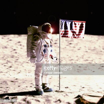 An astronaut next to an American flag on the moon