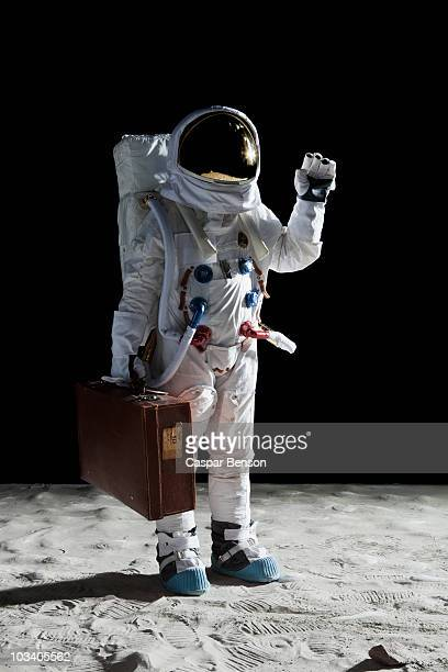 An astronaut on the moon carrying a suitcase and waving