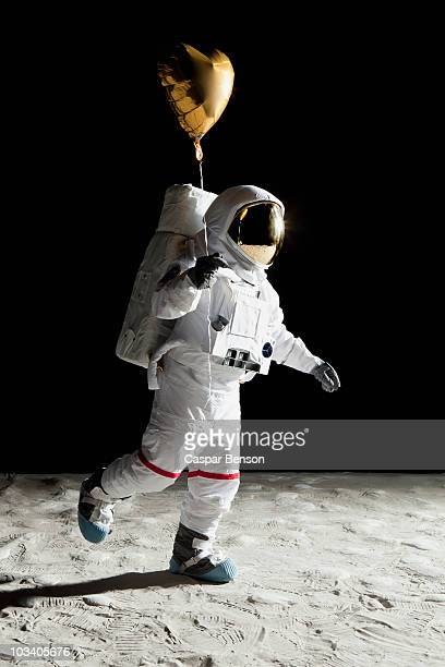 An astronaut on the moon holding a heart shaped helium balloon