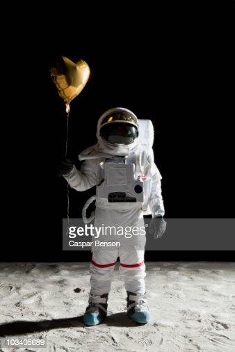 An Astronaut On The Moon Holding A Heart Shaped Helium ...