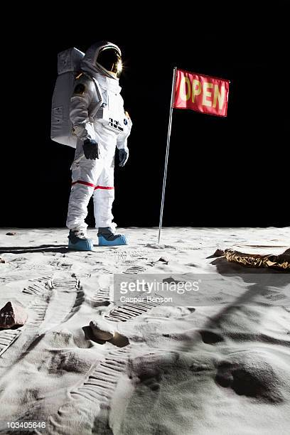 An astronaut on the moon next to a flag with OPEN on it