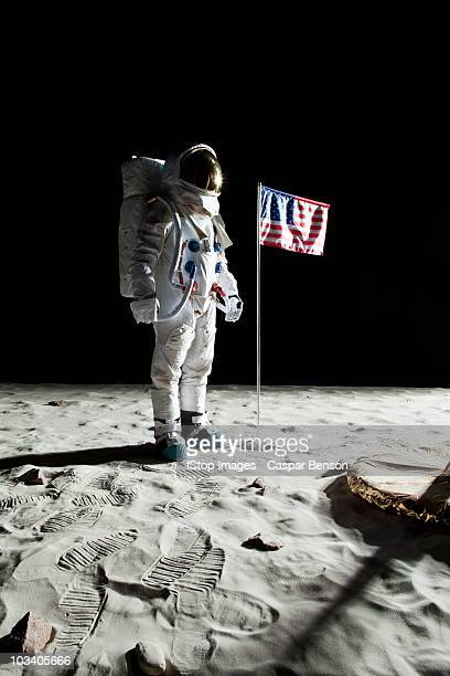 An astronaut on the moon standing next to an American flag