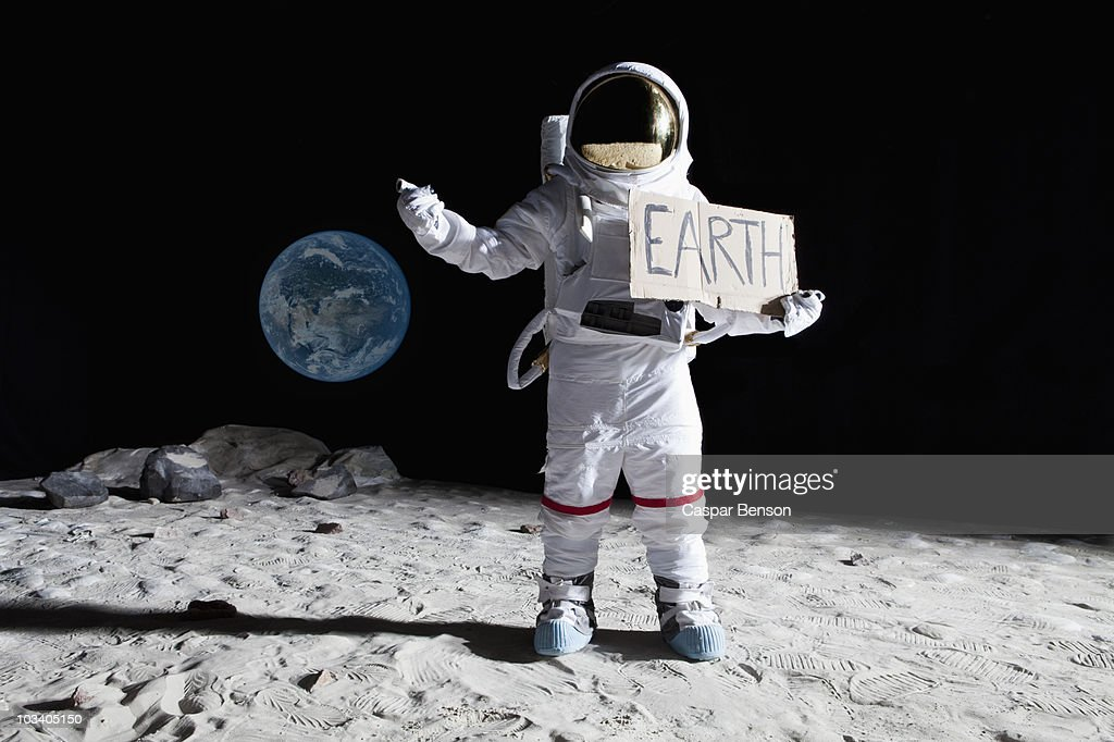An Astronaut On The Moon With His Thumb Out Holding Earth ...