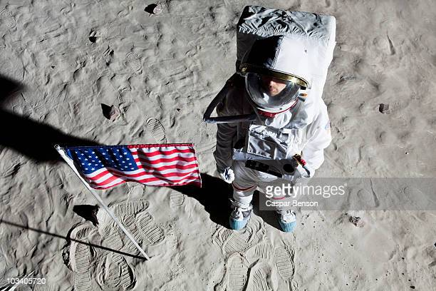 An astronaut on the surface of the moon next to an American flag