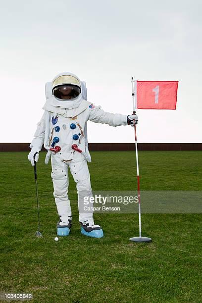 An astronaut posing on a putting green