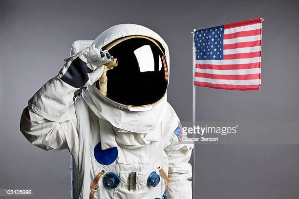 An astronaut saluting next to an American flag, studio shot