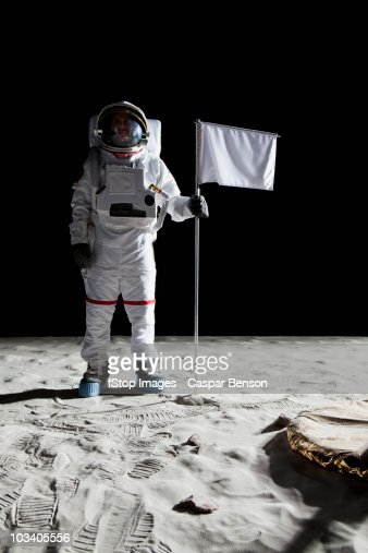 An astronaut standing next to a white flag