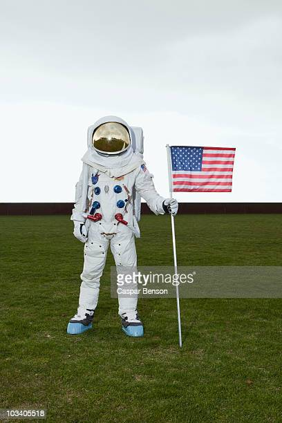 An astronaut standing on a lawn while posing next to an American flag