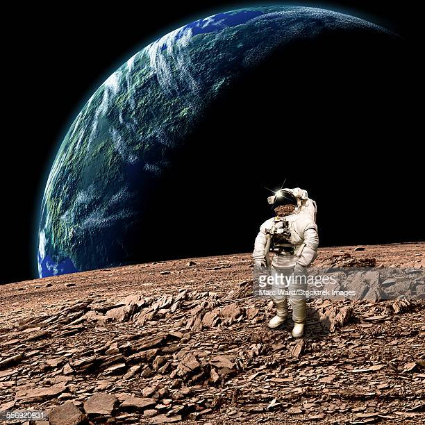 An astronaut surveys his situation after being marooned on a barren planet. An Earth-like planet shines in the background.