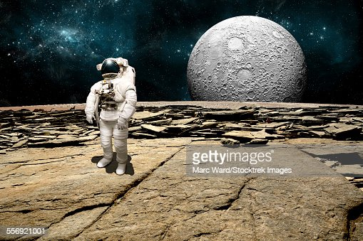 An astronaut surveys his situation after being marooned on a barren planet. A large, heavily crated moon rises over the horizon.