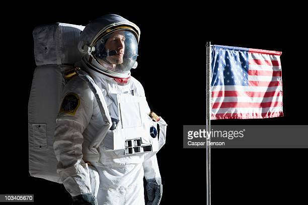 An astronaut with a serious expression standing next to an American flag