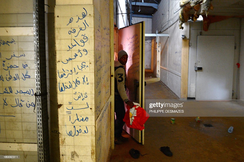 An asylum seeker and refugee leaves on January 18, 2013 a room of a former butcher shop in Dijon, eastern France. One hundred people, mainly men, from African and Eastern European countries live in this old industrial plant before its destruction at the end of winter.