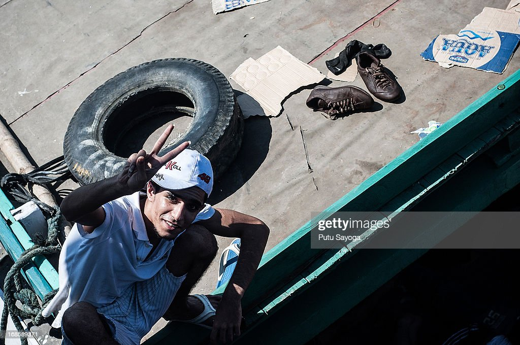 An asylum seeker gestures aboard a boat on May 12, 2013 in Bali, Indonesia. Indonesian police have intercepted an asylum seeker boat harboured in Bali that was believed to be heading to Australia. 80 to 100 people of Middle Eastern origin where found in the hull of a wooden boat on Benoa Harbour.