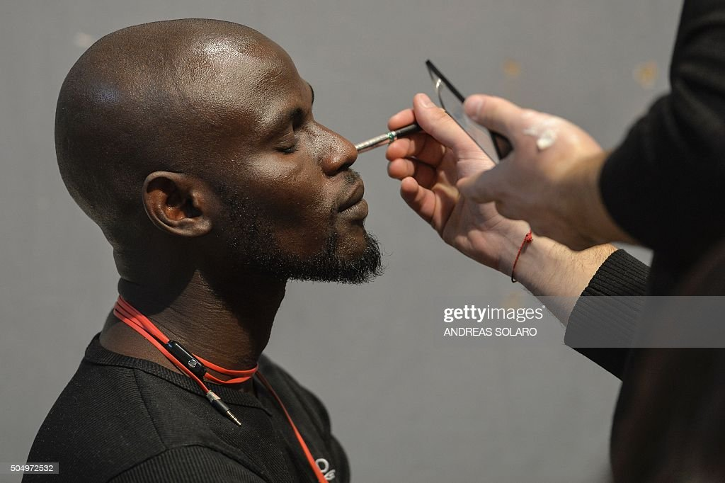An asylum seeker gets his makeup done backstage prior to taking part in the special event 'Generation Africa' during the ITC Ethical Fashion...