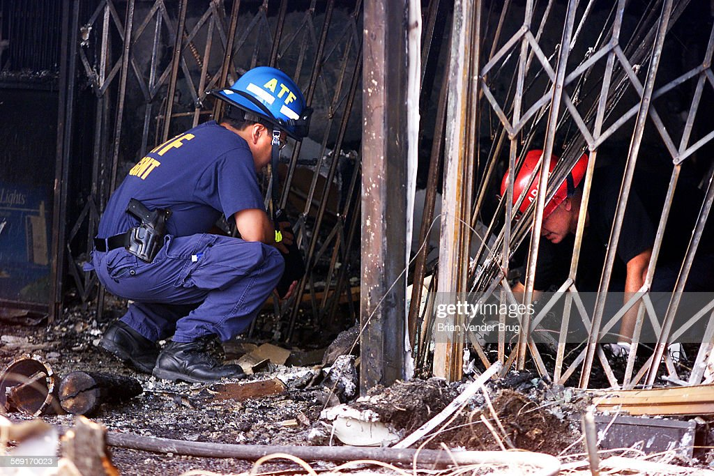 An ATF agent left and an LA City arson investigator right search for clues in the aftermath a of fire that ripped through a strip mall destroying...