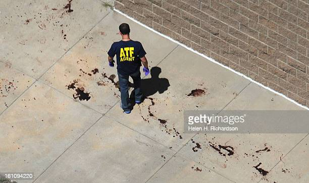 An ATF agent walks around blood stains on the sidewalk on the back side of the theatre Suspected gunman James Holmes is thought to have gunned down...