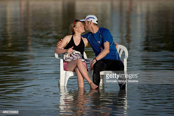 An athlete and his couple kisses themselves sitted on chairs placed at the seashore at Alcudia beach at sunset after the Ironman 703 Mallorca on May...