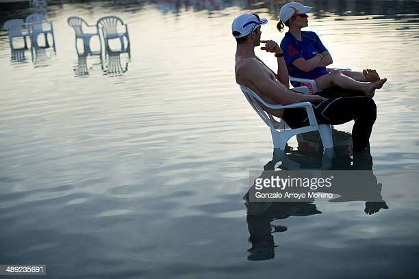 An athlete and his couple rest sitted on chairs placed at the seashore at Alcudia beach at sunset after the Ironman 703 Mallorca on May 10 2014 in...
