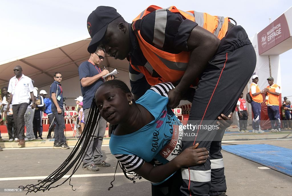 An athlete grabs a firefighter at the start of the first ever Dakar International Marathon organised by the BTP Eiffage society on February 13, 2016 where thousands of people including numerous teenagers and children, took part in the two-day tournament. The competition started on February 13 in front of International Conference Center Abou Diouf (Cicad) on the outskirts of Dakar with different runs of 10 km and will end the day after, February 14, with a marathon. The BTP Eiffage society hosted the event to celebrates its 90 years of presence in Senegal. / AFP / SEYLLOU