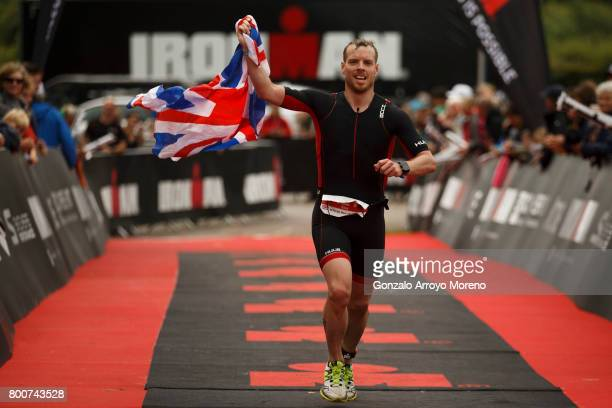 An athlete holds the Union Jack flag as he crosses the finish line during the Ironman 703 UK Exmoor at Wimbleball Lake on June 25 2017 in Somerset...