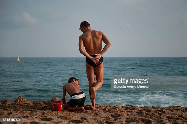 An athlete plays with a kid on the beach the day before of the Ironman Barcelona on October 1 2016 in Calella Spain