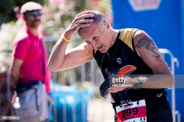 An athlete refreshes during the run leg of Ironman 703 Italy race on June 18 2017 in Pescara Italy