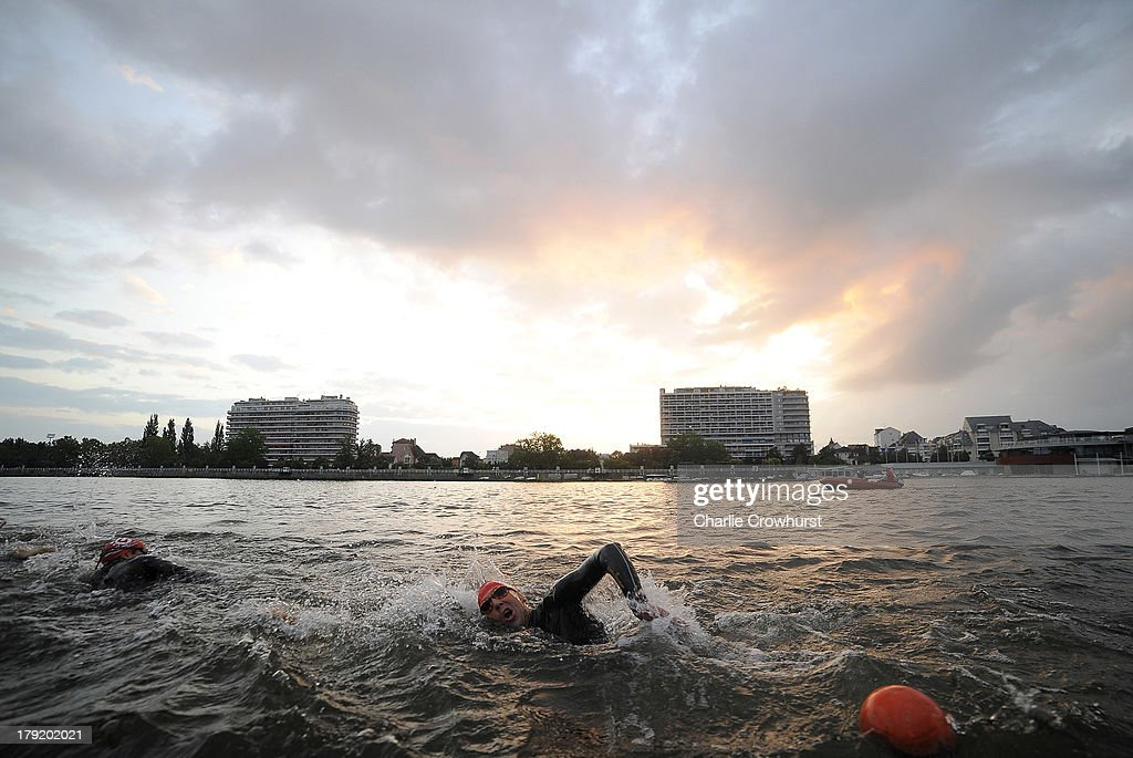 An athlete swims while the sun rises during the Challenge Triathlon Vichy on September 01, 2013 in Vichy, France.