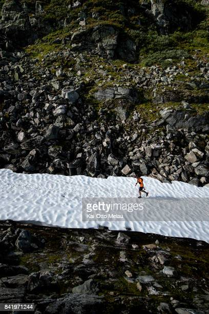 An Athlete walking up the snowy parts of the trail at Hardangervidda Marathon on September 2 2017 in Eidfjord Norway Hardangervidda Marathon goes...