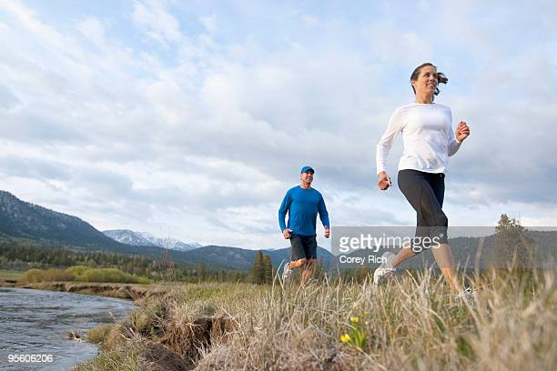 An athletic couple trail running through a field next to a river.