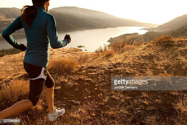 An athletic woman trail running.