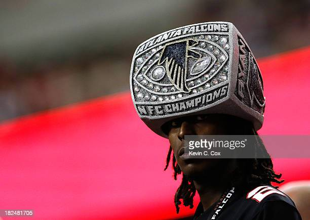 An Atlanta Falcons fan watches the game wearing a hat shaped like an NFC Championship ring during the game against the New England Patriots at...