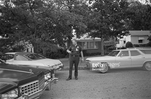 An Atlanta policeman directs traffic in front of the home of Wayne B Willaims after Williams was arrested and charged with the murder of Nathaniel...