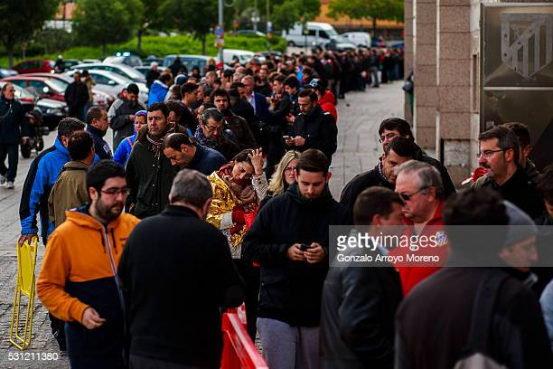 An Atletico de Madrid fan covered with a foil blanket reacts as she queues up to purchase a ticket for the UEFA Champions League Final between Club...