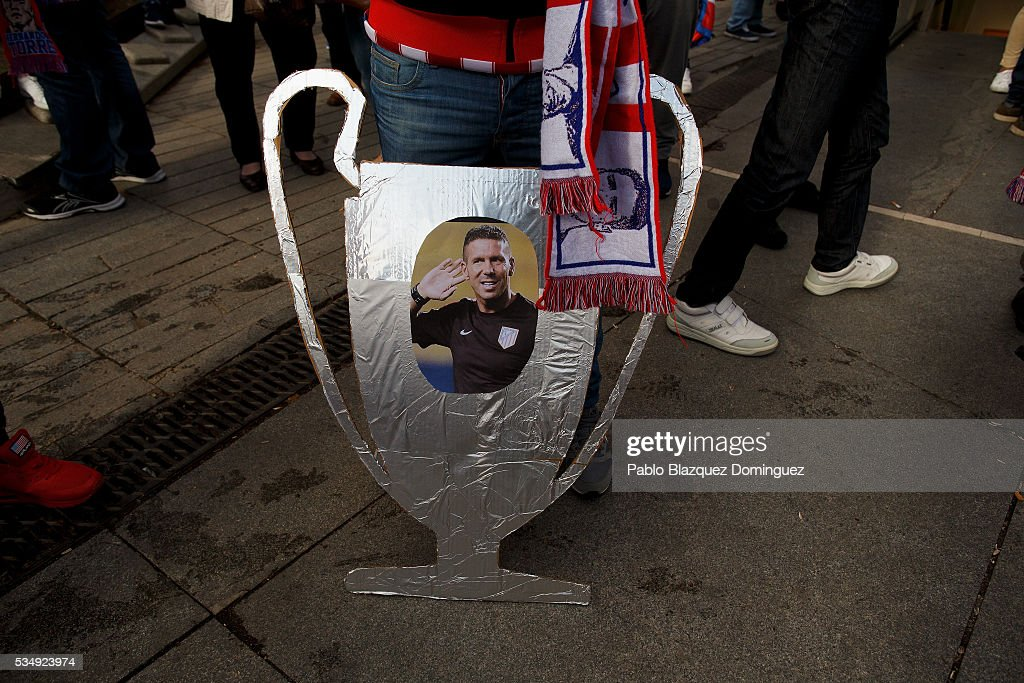An Atletico de Madrid fan holds a cut carboards depicting Champions League Trophy with a picture of Diego Simeone outside the Barclaycard Center before the UEFA Champions League Final match between Real Madrid CF and Club Atletico de Madrid on May 28, 2016 in Madrid, Spain. Real Madrid CF and Atletico de Madrid play the final match of the UEFA Champions League in Milan.