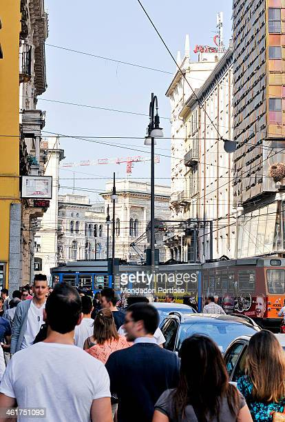 An ATM tram crossing the crowded via Torino There are the entrance arch of the Galleria Vittorio Emanuele II and the facade Geox Breathing Building...