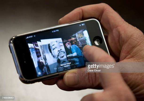 An ATT representative demonstrates the Apple iPhone at the ATT cellular store June 29 2007 in Houston Texas Hundreds of people waited in line at the...