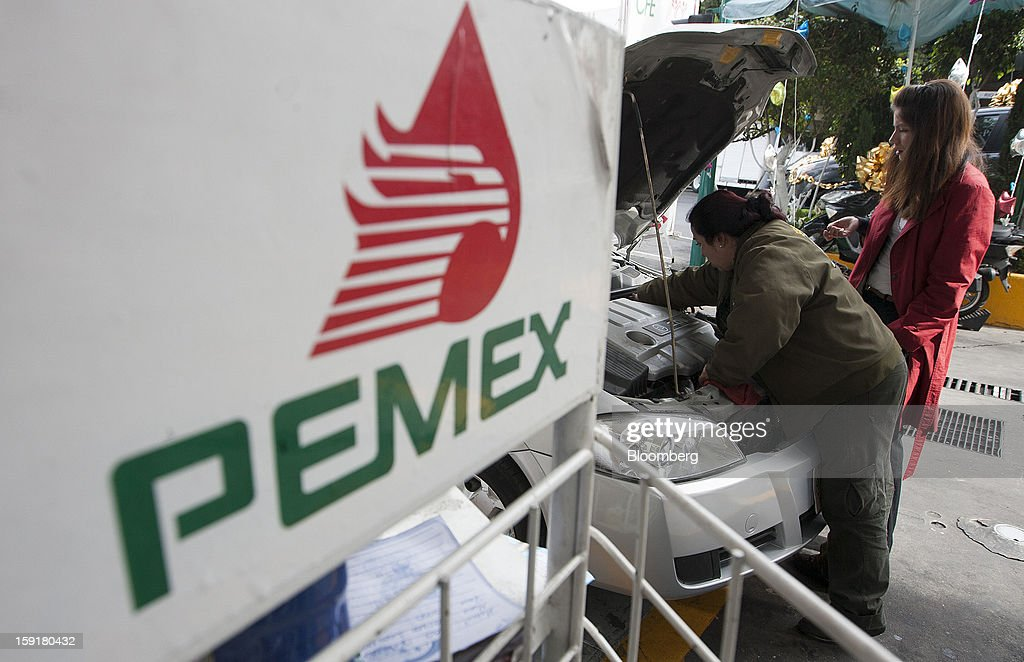 An attendant checks a custmer's engine at a Pemex station in Mexico City, Mexico, on Tuesday, Jan. 8, 2013. Mexico's government is speeding up the removal of subsidies on gasoline and increasing local unleaded gasoline prices by 11 centavos in January, according to the Finance Ministry. Photographer: Susana Gonzalez/Bloomberg via Getty Images