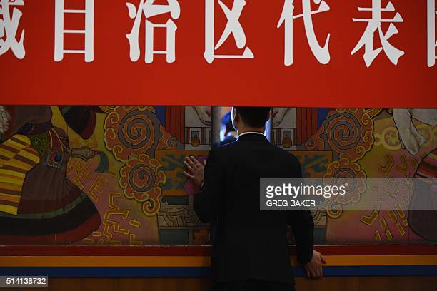 An attendant closes the door after a group meeting for Tibetan delegates at the National People's Congress in Beijing's Great Hall of the People on...