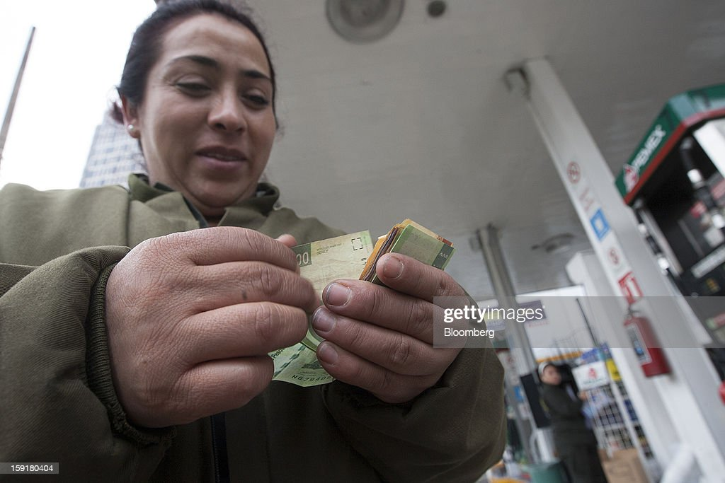 An attendant counts money at a Pemex station in Mexico City, Mexico, on Tuesday, Jan. 8, 2013. Mexico's government is speeding up the removal of subsidies on gasoline and increasing local unleaded gasoline prices by 11 centavos in January, according to the Finance Ministry. Photographer: Susana Gonzalez/Bloomberg via Getty Images