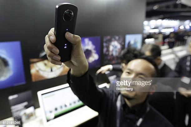 An attendant demonstrates a Ricoh Co Theta 360degree spherical panoramic digital camera at the CP Camera and Photo Imaging Show in Yokohama Kanagawa...