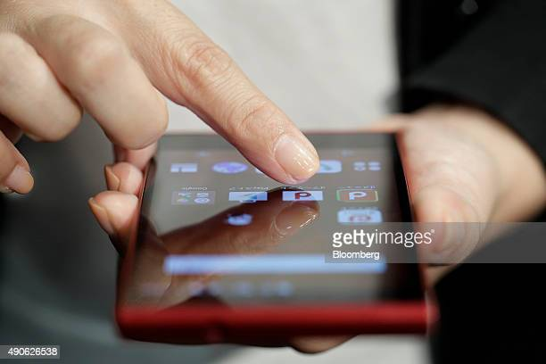 An attendant demonstrates NTT Docomo Inc's Arrows Fit smartphone manufactured by Fujitsu Ltd for a photograph at an unveiling in Tokyo Japan on...