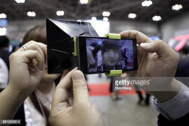 An attendant demonstrates Tenyo Co's Air Sign Kit on a smartphone at the International Tokyo Toy Show in Tokyo Japan on Thursday June 1 2017 The toy...