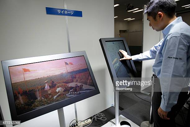 An attendant demonstrates the touch panel function on a reflective color liquid crystal display developed by Japan Display Inc presented as a guide...