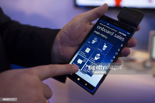 An attendant demonstrates the use of the Avanade Mobile Airline Platform developed by Microsoft Corp and Avanade Inc for processing inflight sales...