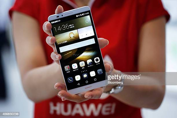 An attendant displays a Huawei Technologies Co Ascend Mate7 smartphone at the CuttingEdge IT Electronics Comprehensive Exhibition in Chiba Japan on...