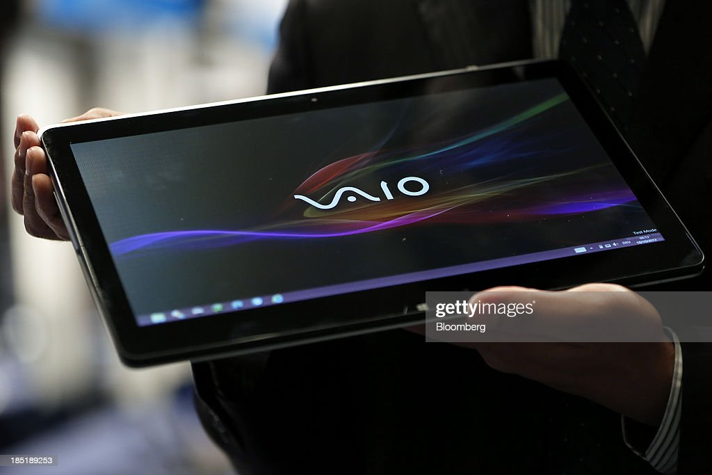 An attendant displays a Sony Corp. Vaio Fit laptop computer, running Microsoft Corp.'s Windows 8 operating system, during a launch event for the operating system in Tokyo, Japan, on Friday, Oct. 18, 2013. Microsoft Chief Executive Officer Steve Ballmer, who will be retiring within a year, said the company is still working to make sure that the personal computer remains relevant as 'the device of choice.' Photographer: Kiyoshi Ota/Bloomberg via Getty Images
