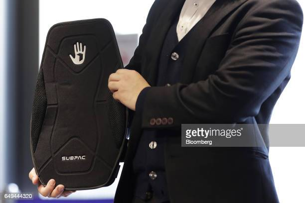 An attendant displays a SubPac Inc S2 seatback tactile bass system for a photograph at a SoftBank Corp Style media event in Tokyo Japan on Wednesday...