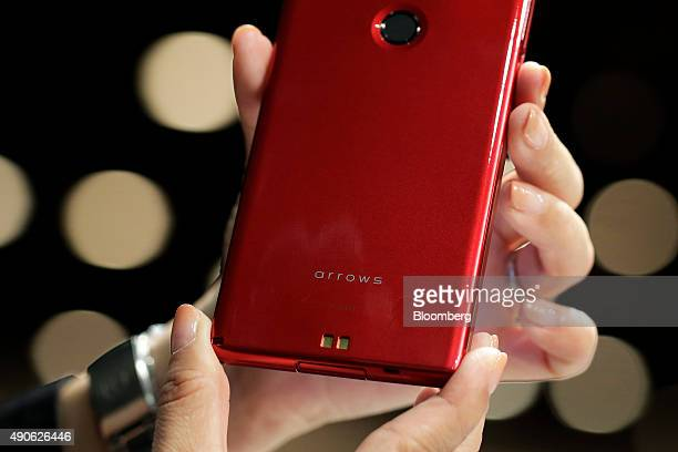 An attendant displays NTT Docomo Inc's Arrows Fit smartphone manufactured by Fujitsu Ltd for a photograph at an unveiling in Tokyo Japan on Wednesday...