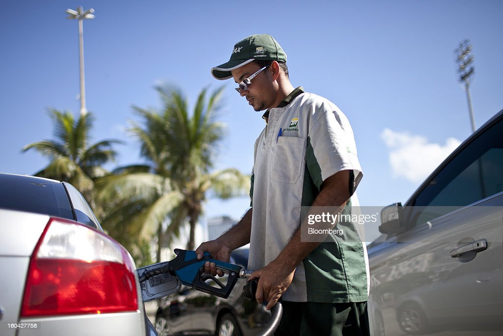 An attendant fills a vehicle's gas tank at a Petroleo Brasileiro SA (Petrobras) station in Rio de Janeiro, Brazil, on Thursday, Jan. 31, 2013. State-controlled oil company Petrobras announced earlier this week that it would raise gasoline and diesel prices by 6.6 percent and 5.4 percent, respectively. Photographer: Dado Galdieri/Bloomberg via Getty Images
