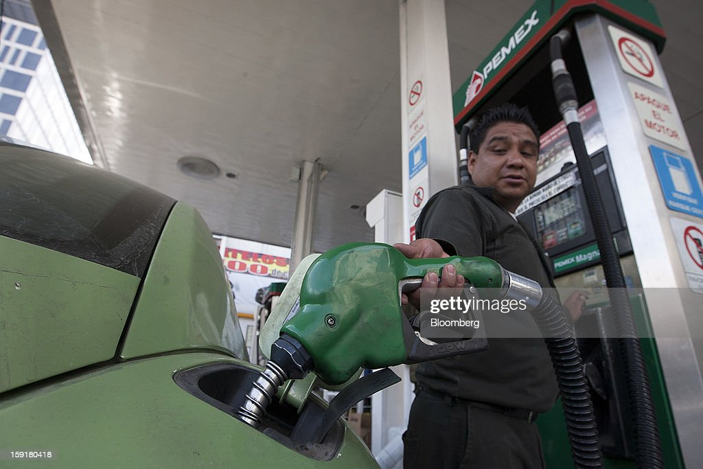 An attendant fills the tank of a car at a Pemex station in Mexico City, Mexico, on Tuesday, Jan. 8, 2013. Mexico's government is speeding up the removal of subsidies on gasoline and increasing local unleaded gasoline prices by 11 centavos in January, according to the Finance Ministry. Photographer: Susana Gonzalez/Bloomberg via Getty Images